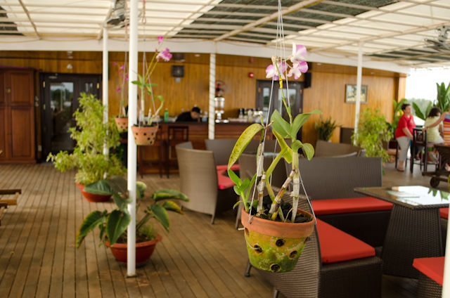 The outdoor Sun Deck, with its covered awning, hanging plants and comfortable loungers, is a great place to watch the Mekong drift by. Photo © 2013 Aaron Saunders