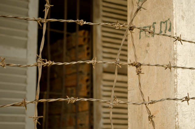 Razor wire was added to the former highschool in 1975 when it was taken over by Pol Pot's Khmer Rouge. Photo © 2013 Aaron Saunders