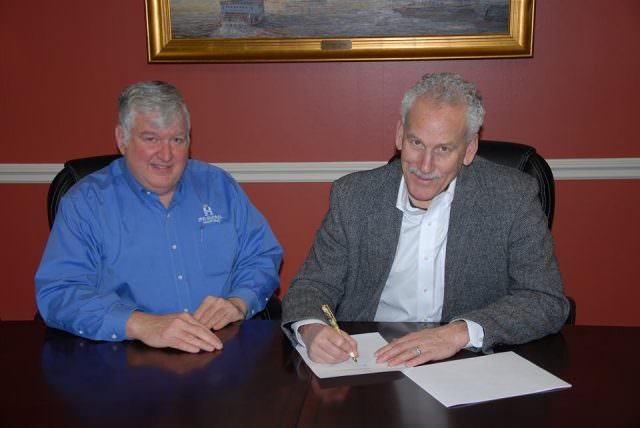 American Queen Steamboat Company Chairman and CEO John Waggoner (right) and HMS Global Maritime In-House Legal Counsel Bob Herre (Left) sign documents officially closing the purchase of the American Empress from the US Maritime Administration. Photo courtesy of American Queen Steamboat Company