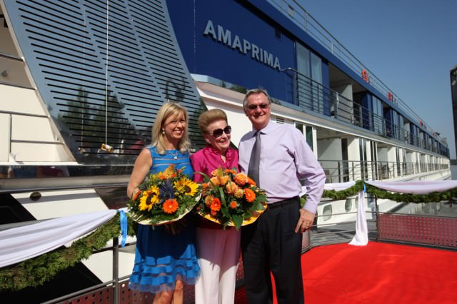 Kristin Karst (left), AmaWaterways' executive vice president, and Rudi Schreiner, president, photographed during a Bavarian christening ceremony of their new ship AmaPrima in Vilshofen, Germany. Kristin is presenting a present to AmaPrima godmother Valerie Wilson. © 2013 Ralph Grizzle