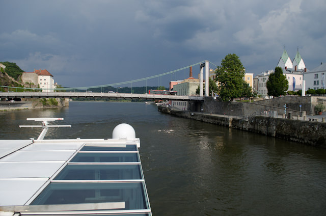 Emerald Star departs Passau under increasingly dark skies. It never rained, but the thunder was very pronounced. Note the windows in the foreground for Emerald Star's swimming pool. Photo © 2014 Aaron Saunders