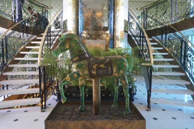 Where some of the $2 million spent on original art surely went: The atrium with its Murano glass horse and waterfall background and stairs descending on both sides. © 2014 Ralph Grizzle