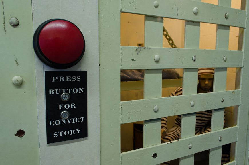 "Push the button and make the convict talk! For kids, it was more convincing: one kid in the room during our visit peered hesitantly through the bars before asking his dad, ""Is he real? Are you real?"" Photo © 2015 Aaron Saunders"