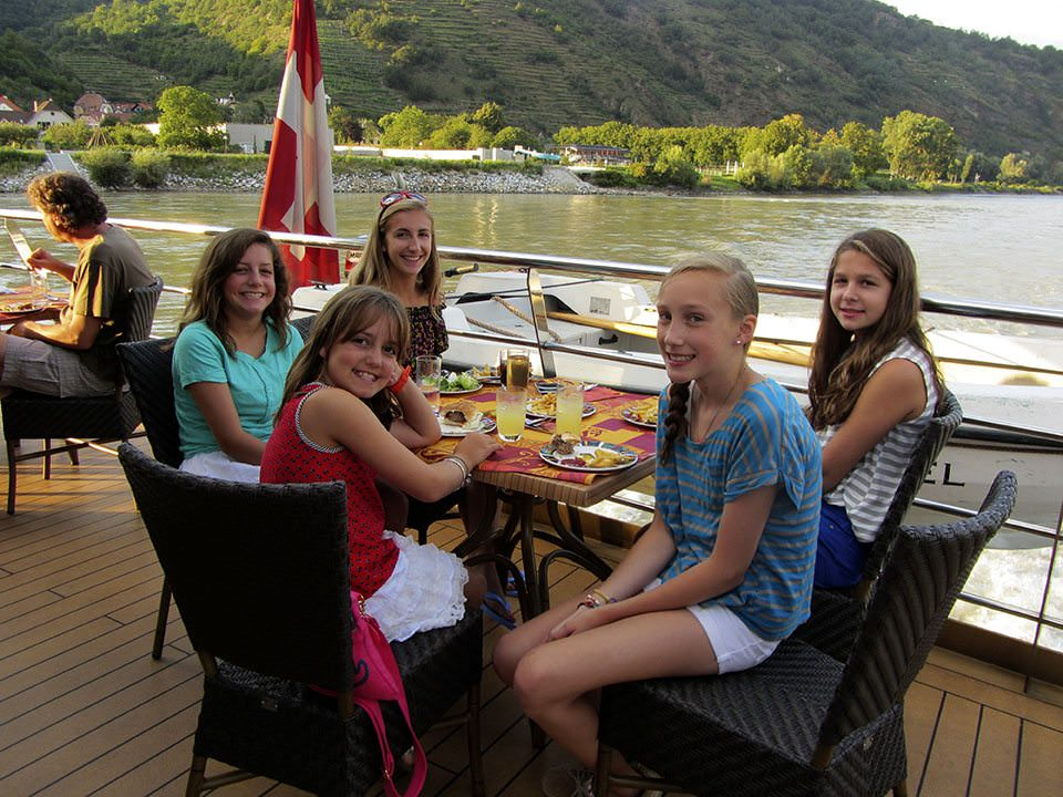 Some lines are more family-friendly than others. Here, guests enjoy lunch out on deck on one of Tauck's Tauck Bridges family river cruises. Photo courtesy of Tauck.