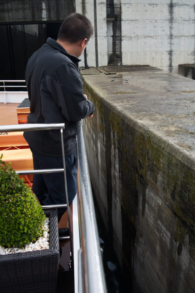 A Viking Torgil crewmember checks our progress as we enter the lock - one of five such ones we'd transit on our journey. Photo © 2015 Aaron Saunders