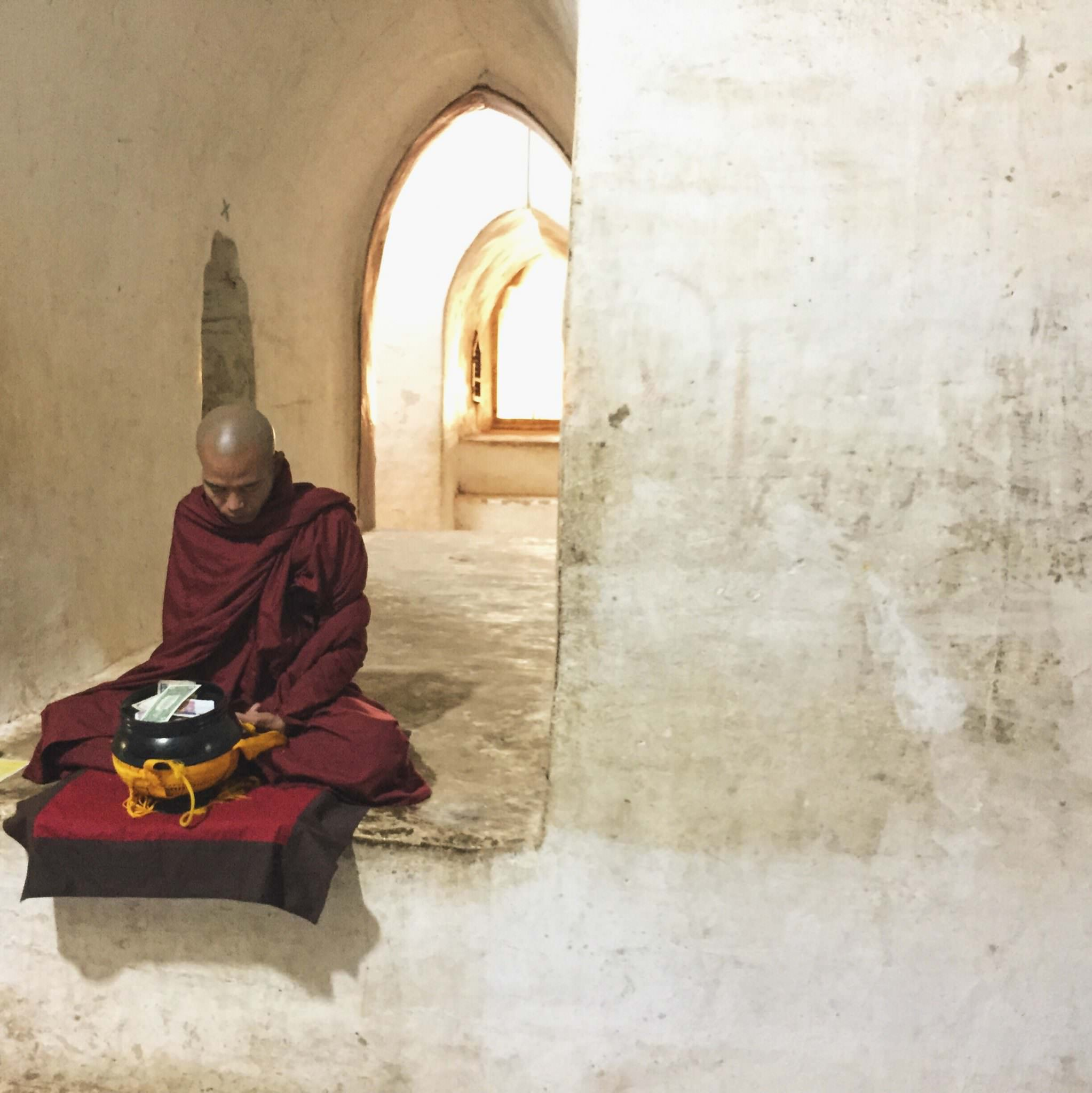 A Buddhist monk prays inside the hallways of the temple, accepting offerings of money or food. © 2015 Gail Jessen