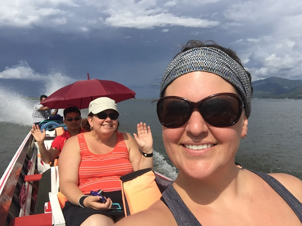 Me, Heather, Nanda, and our captain enjoy perfect weather on the bright blue lake, surrounded by mountain peaks on every side. © 2015 Gail Jessen