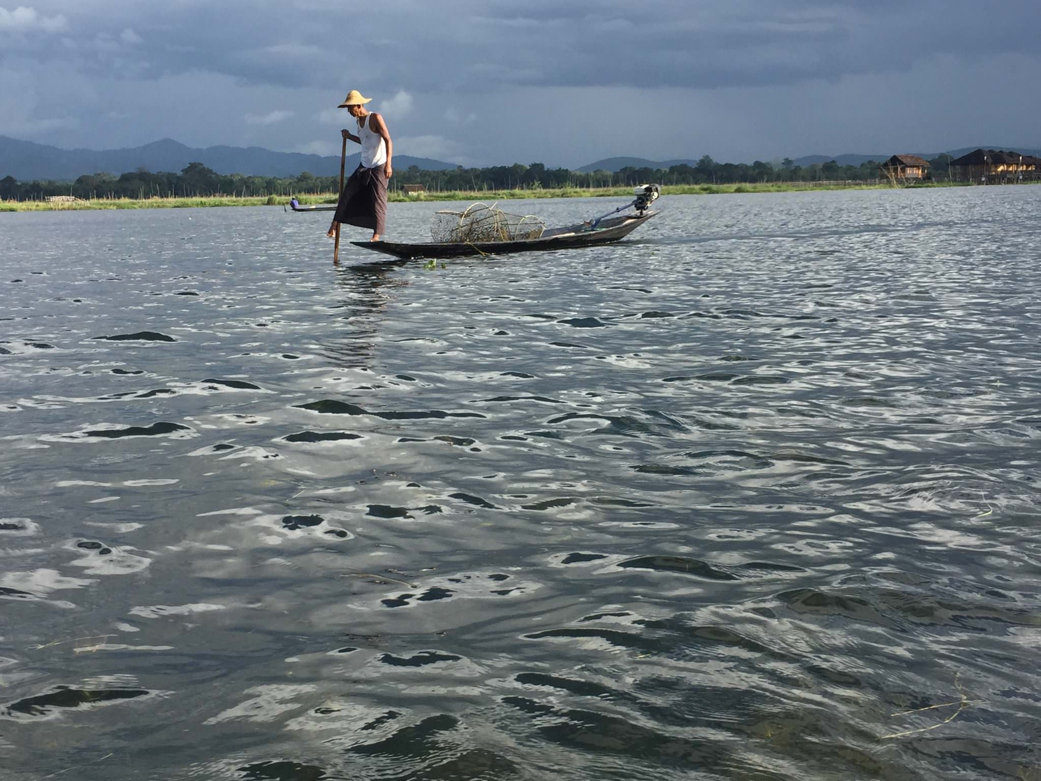 Wearing a traditional longhi around his waist, this fisherman paddles with his boat with his right foot. © 2015 Gail Jessen