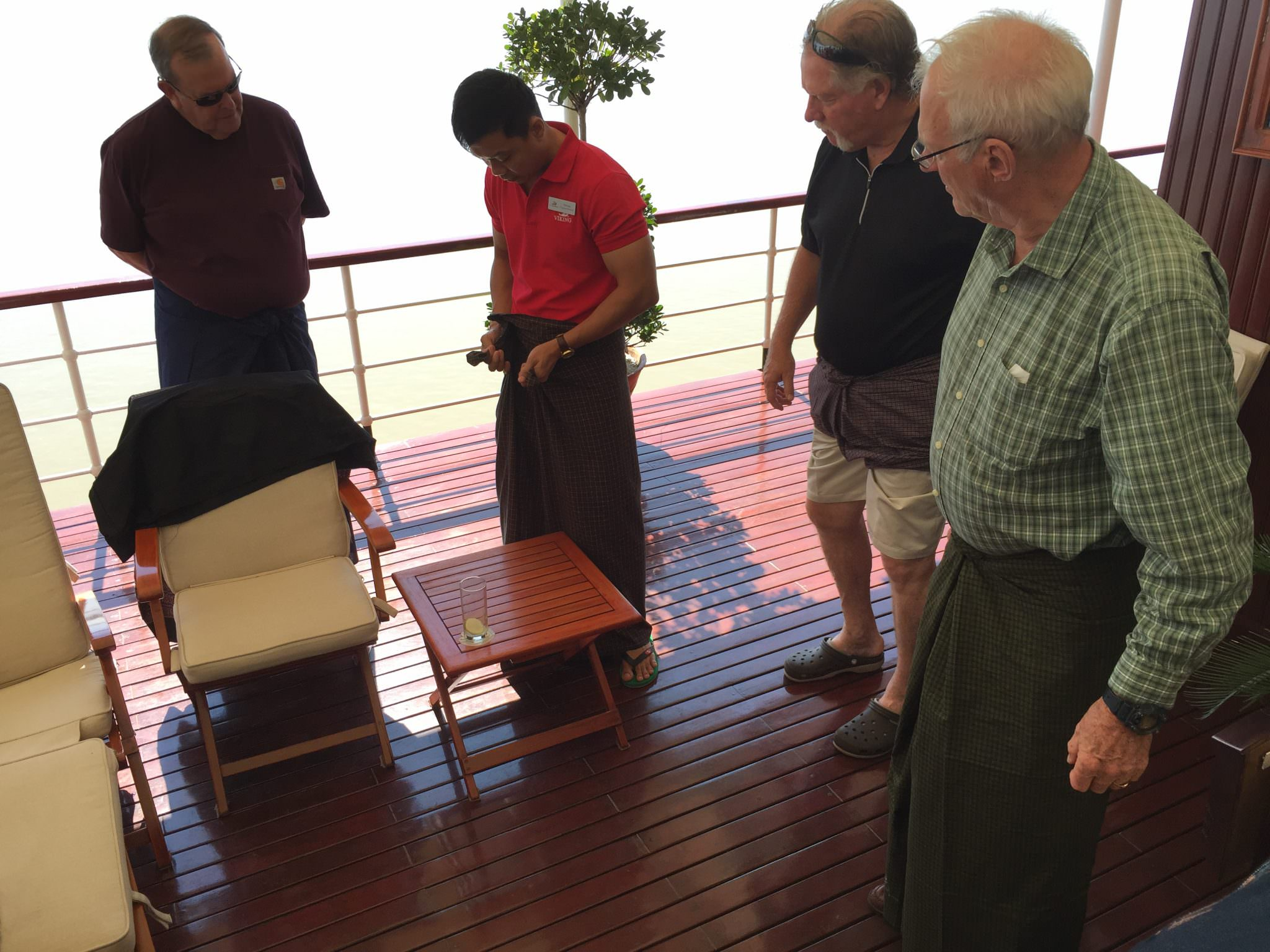 Fellow passengers attempt to wrap and tie their longhis, with one guest going full girding (used when playing sports). Most of the men found them very comfortable and two men wore them to dinner on the ship that night. © 2015 Gail Jessen