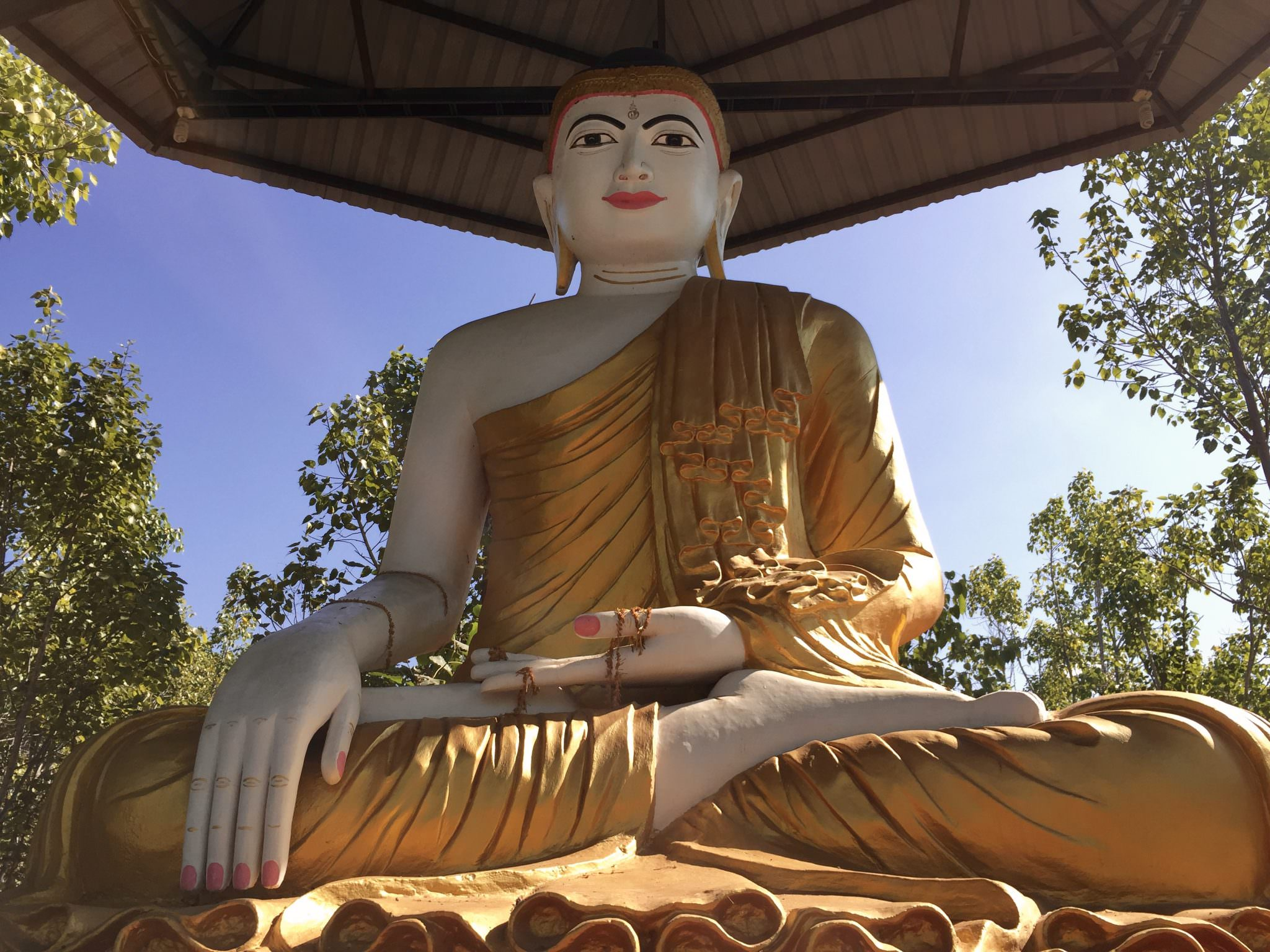 One central statue watches over the park. The mudra of this Buddha's hands symbolizes meditation (left) and not wavering from that practice by staying grounded under the bodhi tree until he achieves enlightenment (right). © 2015 Gail Jessen