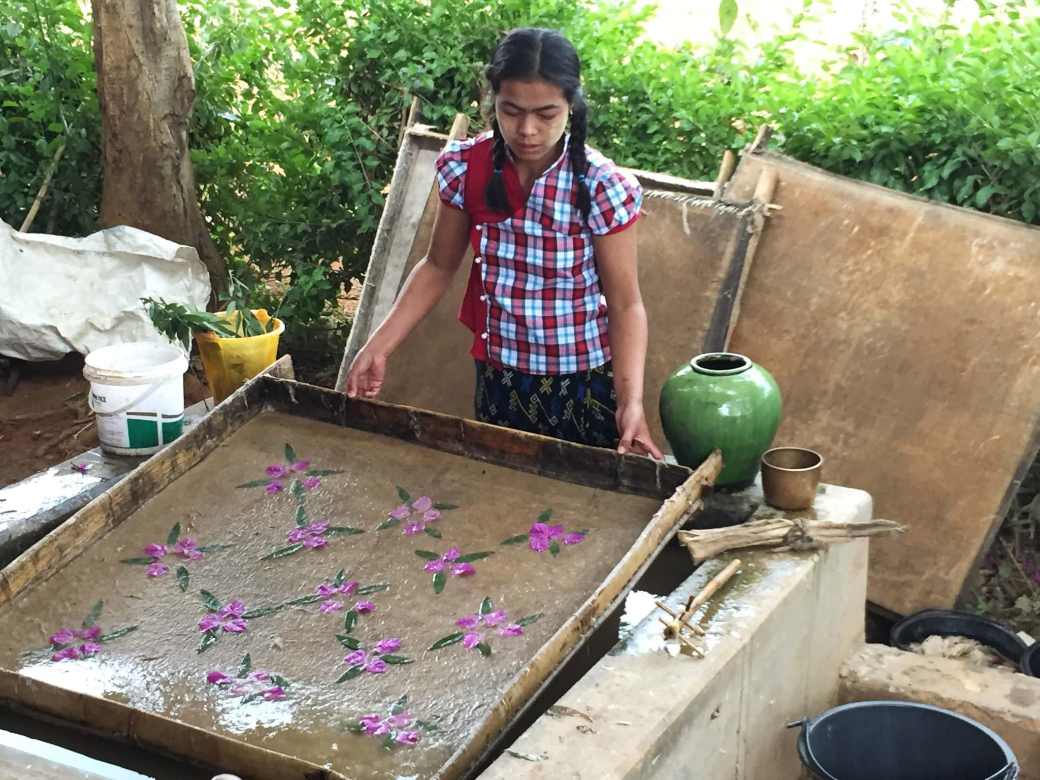 After placing flower petals in the frame that holds the bamboo paper paste, she carefully drains the water through the bamboo. (c) 2015 Gail Jessen