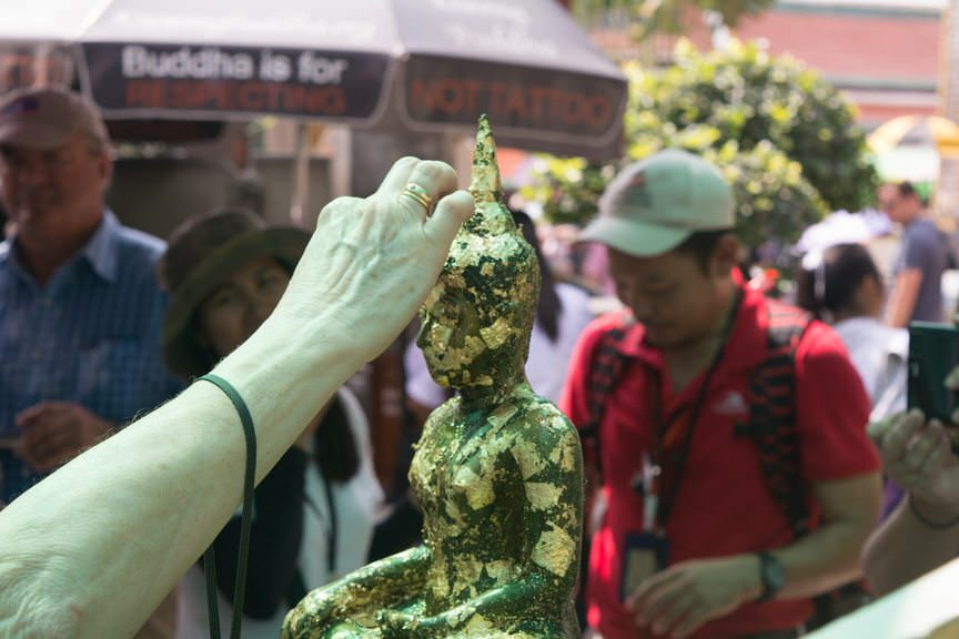 Guests were invited to add gold leaf to Buddha; doing so ensures good luck. Photo © 2015 Aaron Saunders
