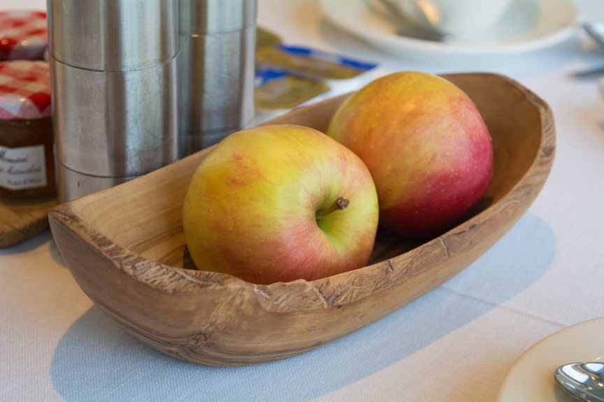 Fresh apples are placed in hand-carved wooden baskets on tables....Photo © 2016 Aaron Saunders